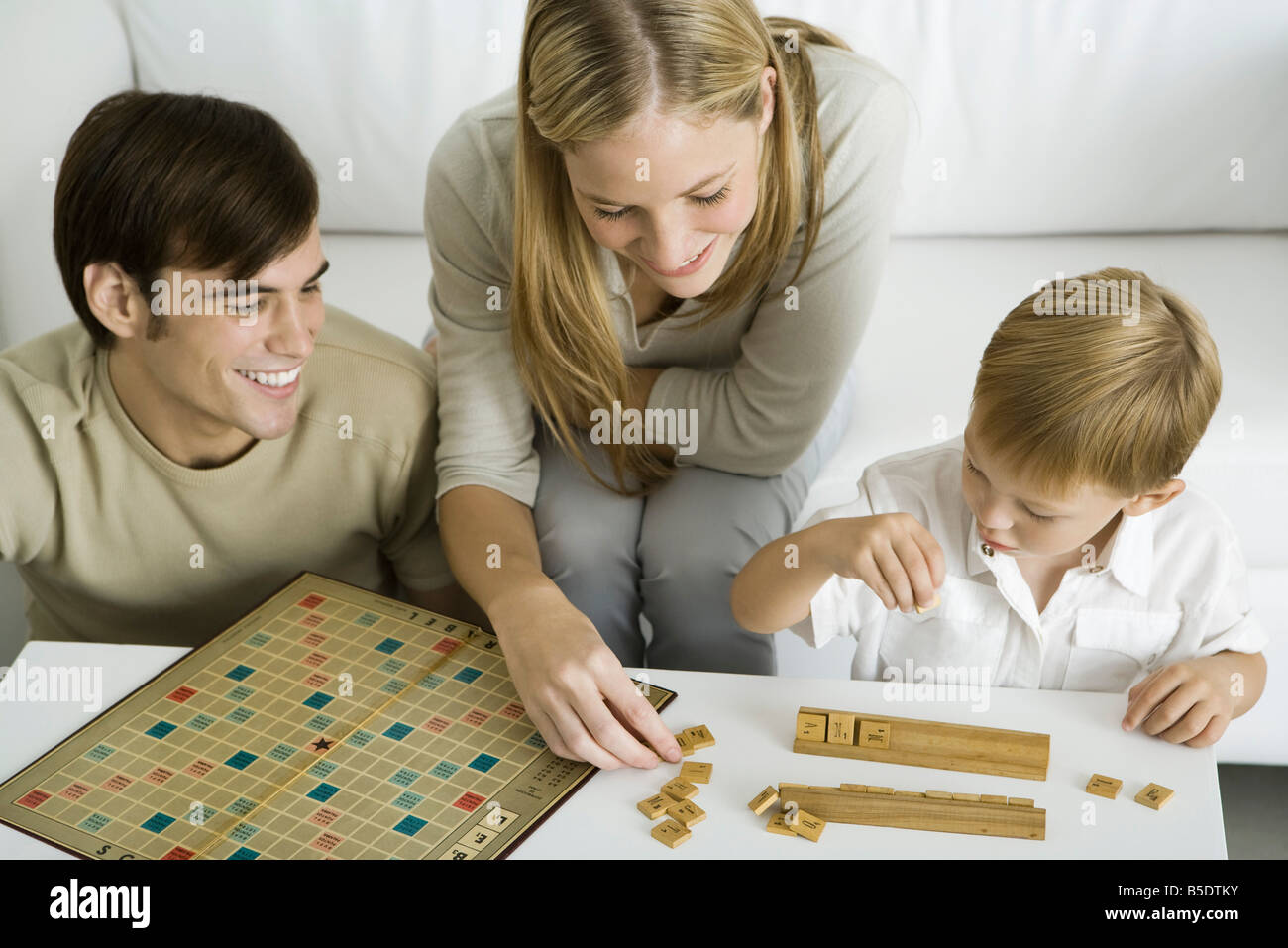 Family playing board game together, mother arranges game pieces - Stock Image