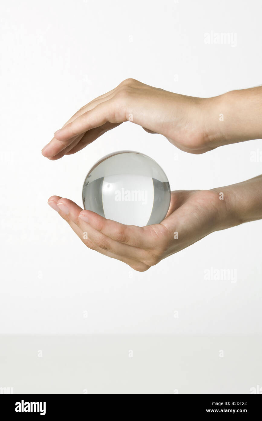 Hands holding crystal ball - Stock Image