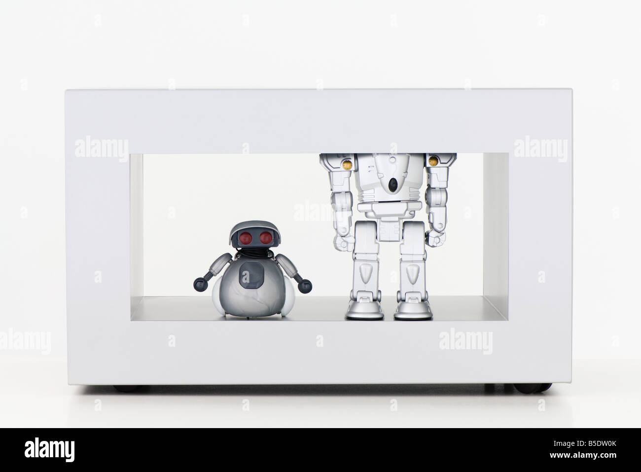 Toy robots standing side by side, one short and the other tall - Stock Image