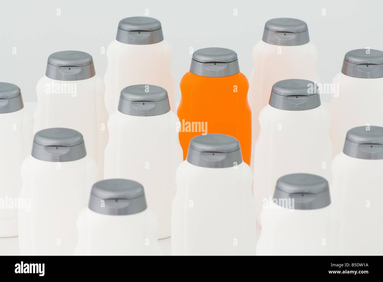 One orange bottle among group of white plastic bottles - Stock Image