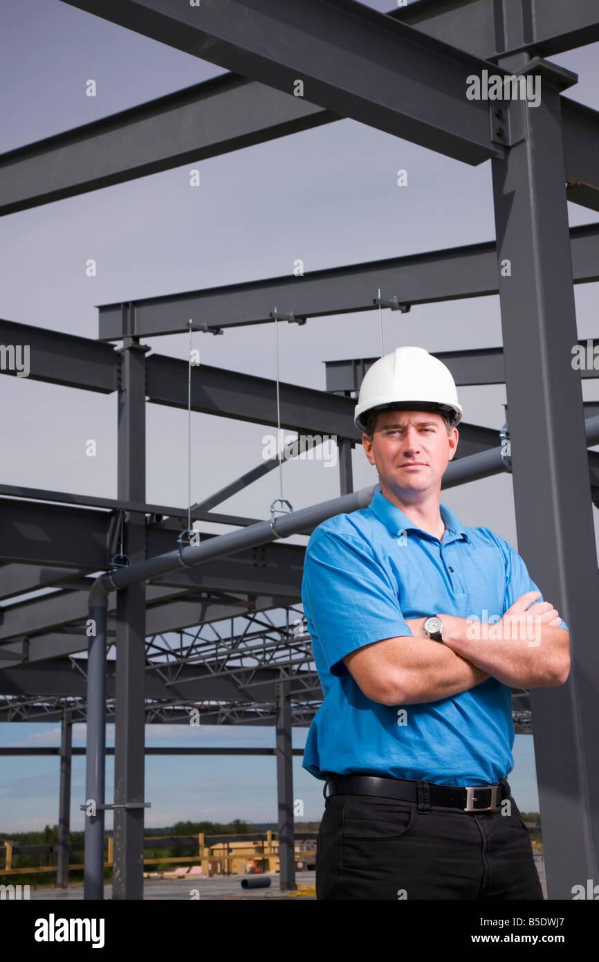 Engineer leaning against metal beam - Stock Image