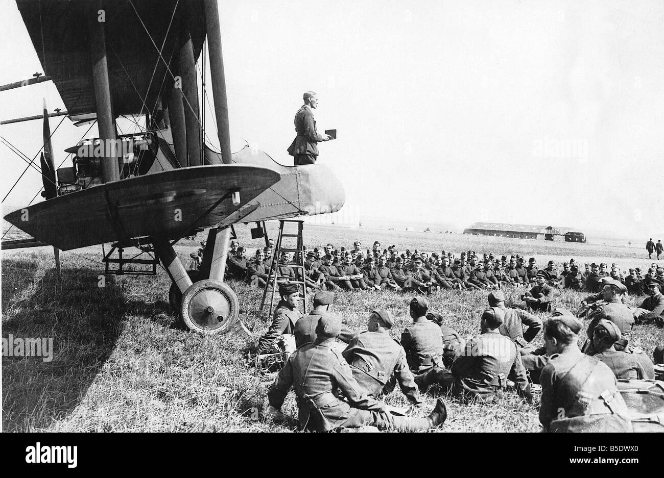 British troops listen to a chaplin delivering his Sunday Morning Service from the open cockpit of a World War One - Stock Image