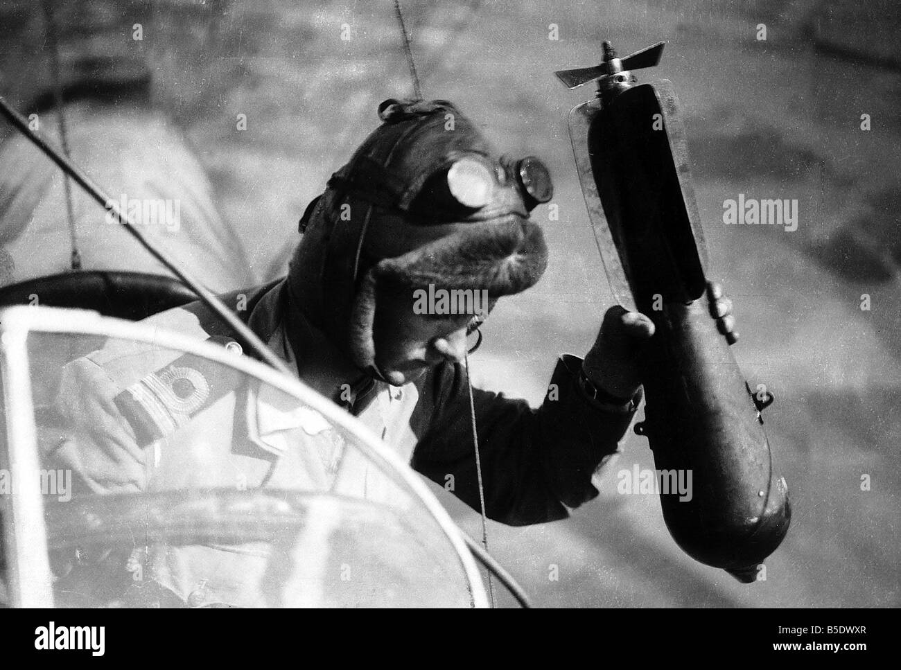 World War One A British airman holding a bomb in his hand looks out of his aircraft taking aim at his target 1917 - Stock Image