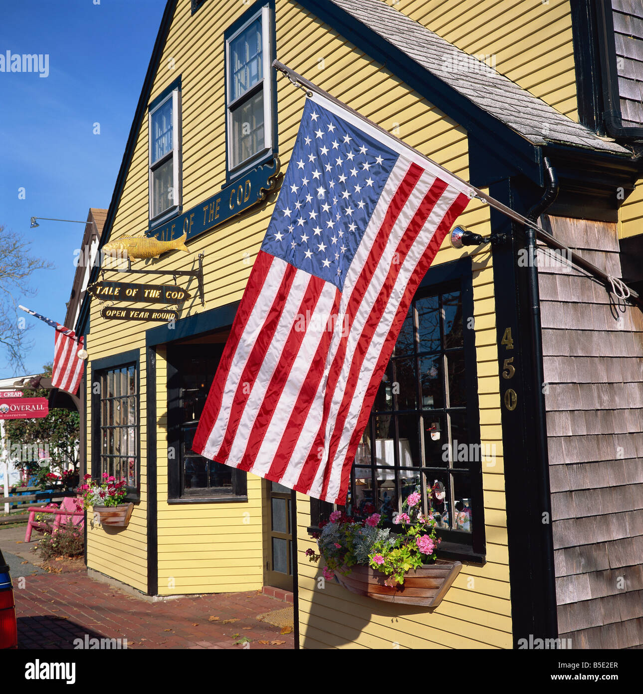 The American flag the stars and stripes flies outside the Tale of the Cod shop in Cape Cod Massachusetts New England - Stock Image