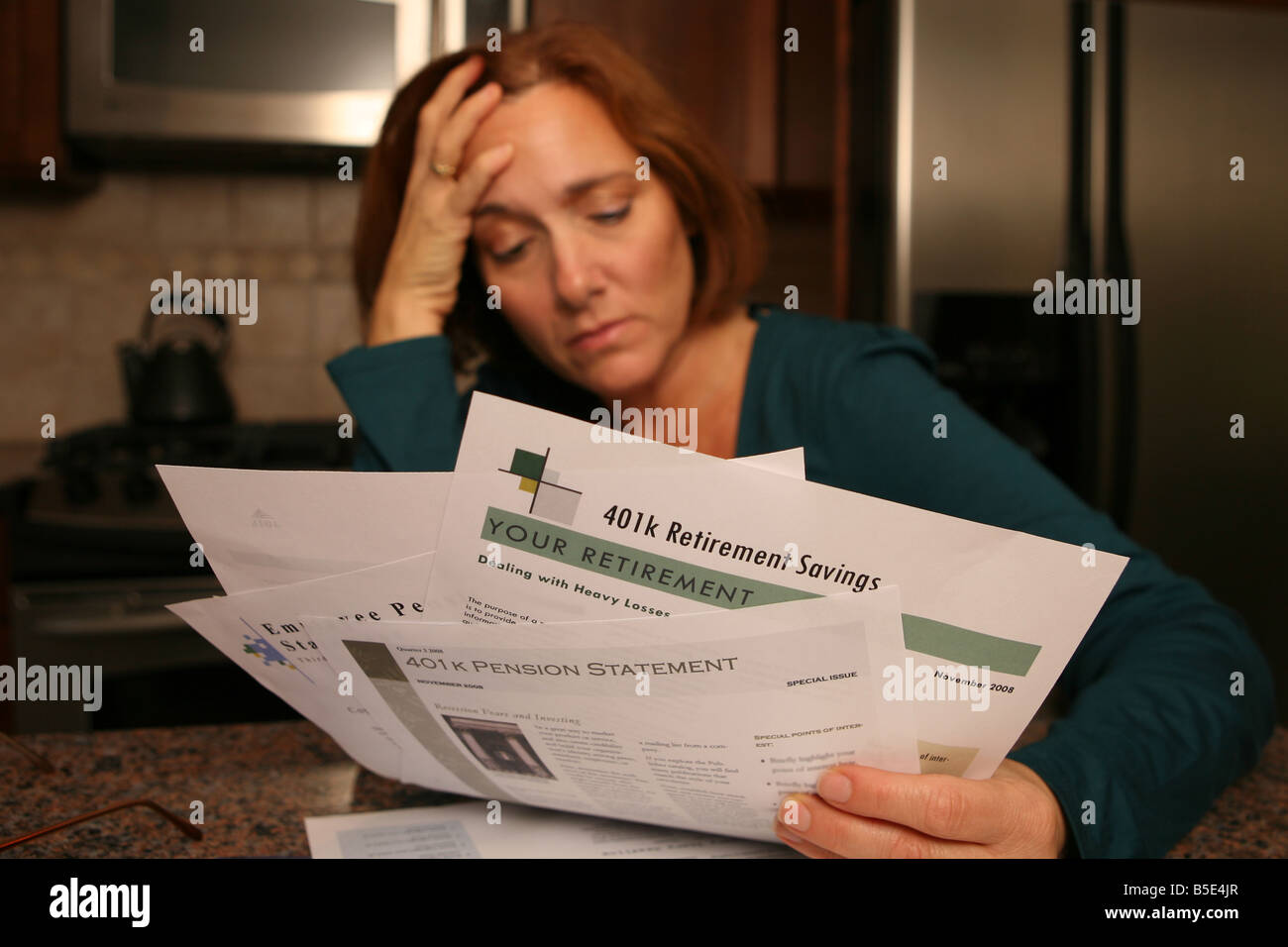 A woman is gripped by worry and anxiety as she looks over her investment statements. - Stock Image