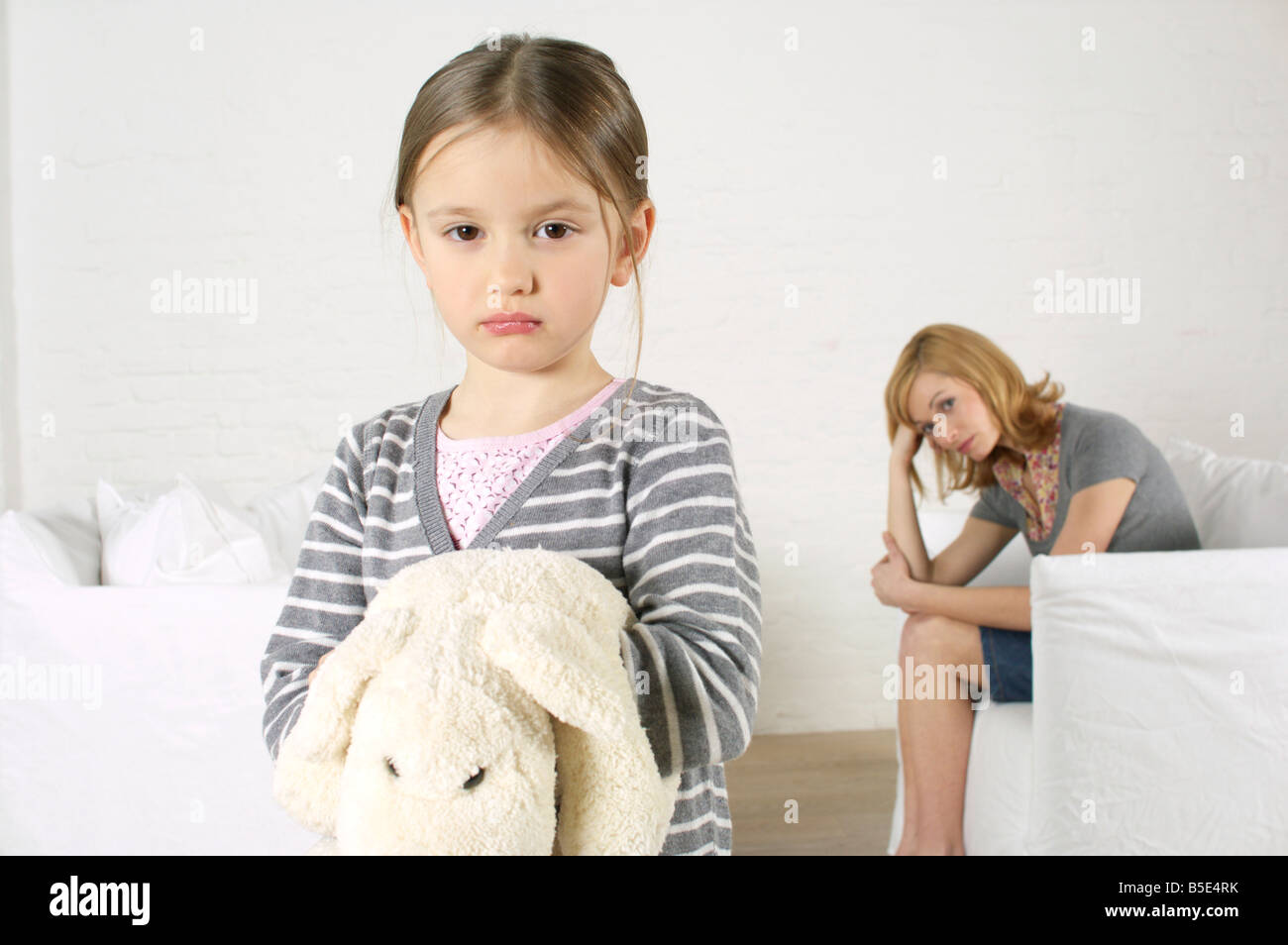 Cheerless girl looking at camera, mother sitting in background Stock Photo