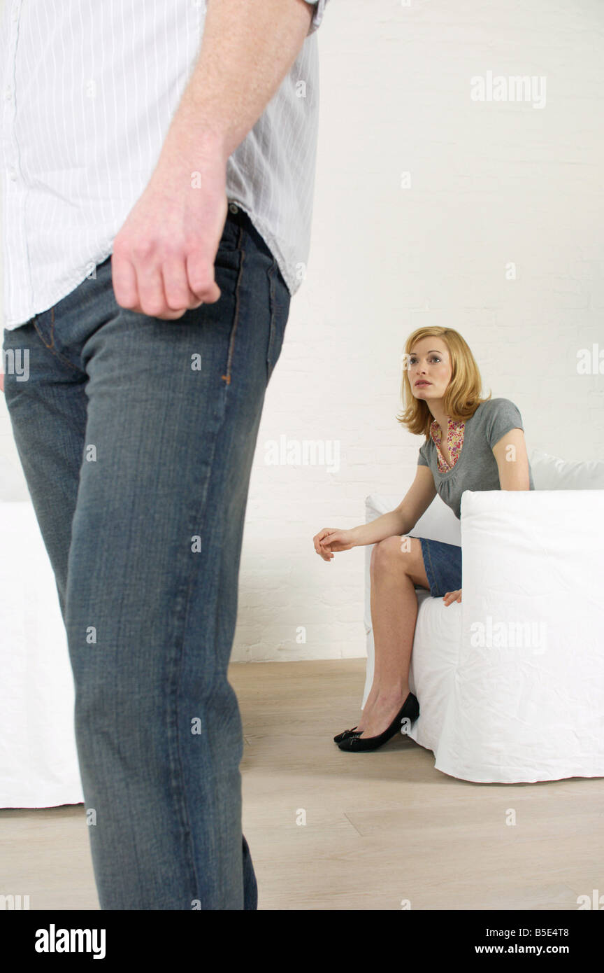 Man going away, frustrated woman sitting in background - Stock Image