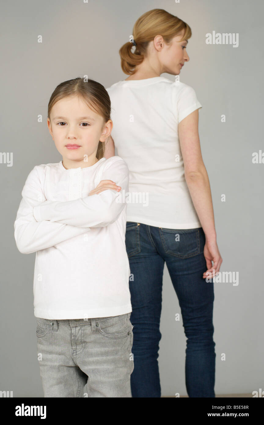Girl looking at camera, mother standing in background - Stock Image