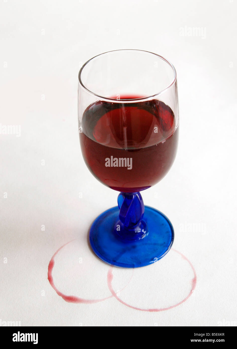 A glass of wine with stains of wine rings on the white table spread. - Stock Image