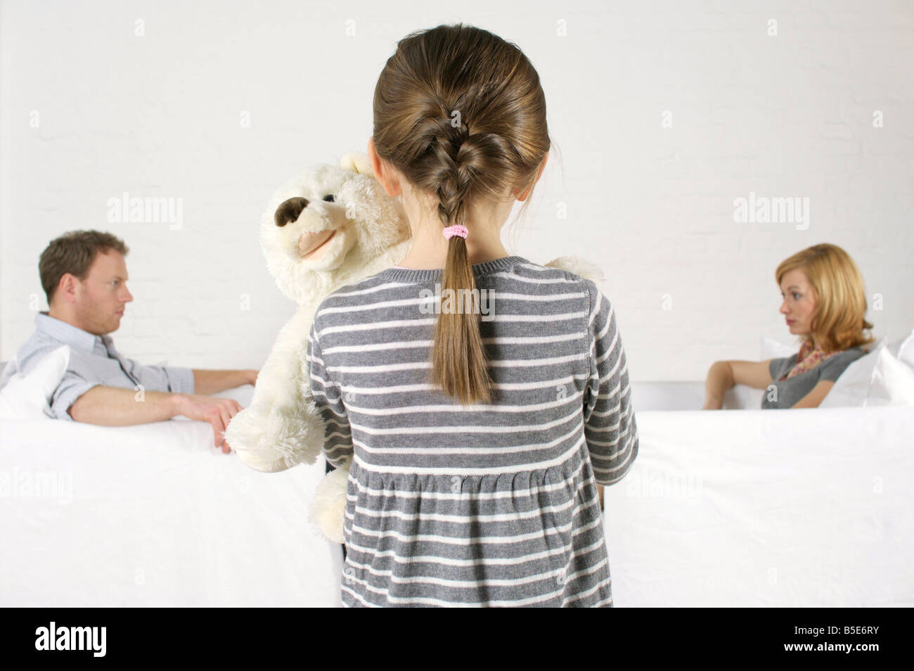 Frustrated couple sitting vis-à-vis, girl holding teddy bear standing in foreground - Stock Image