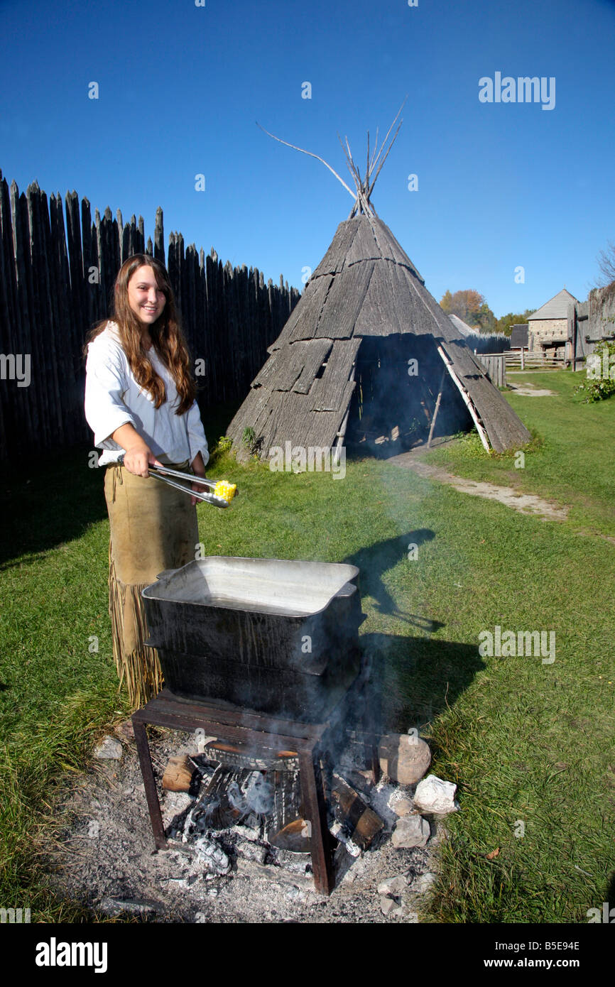 Indian Native woman roasting corn on open fire Corn Roost at Huron Indian Village in Midland Ontario Canada - Stock Image