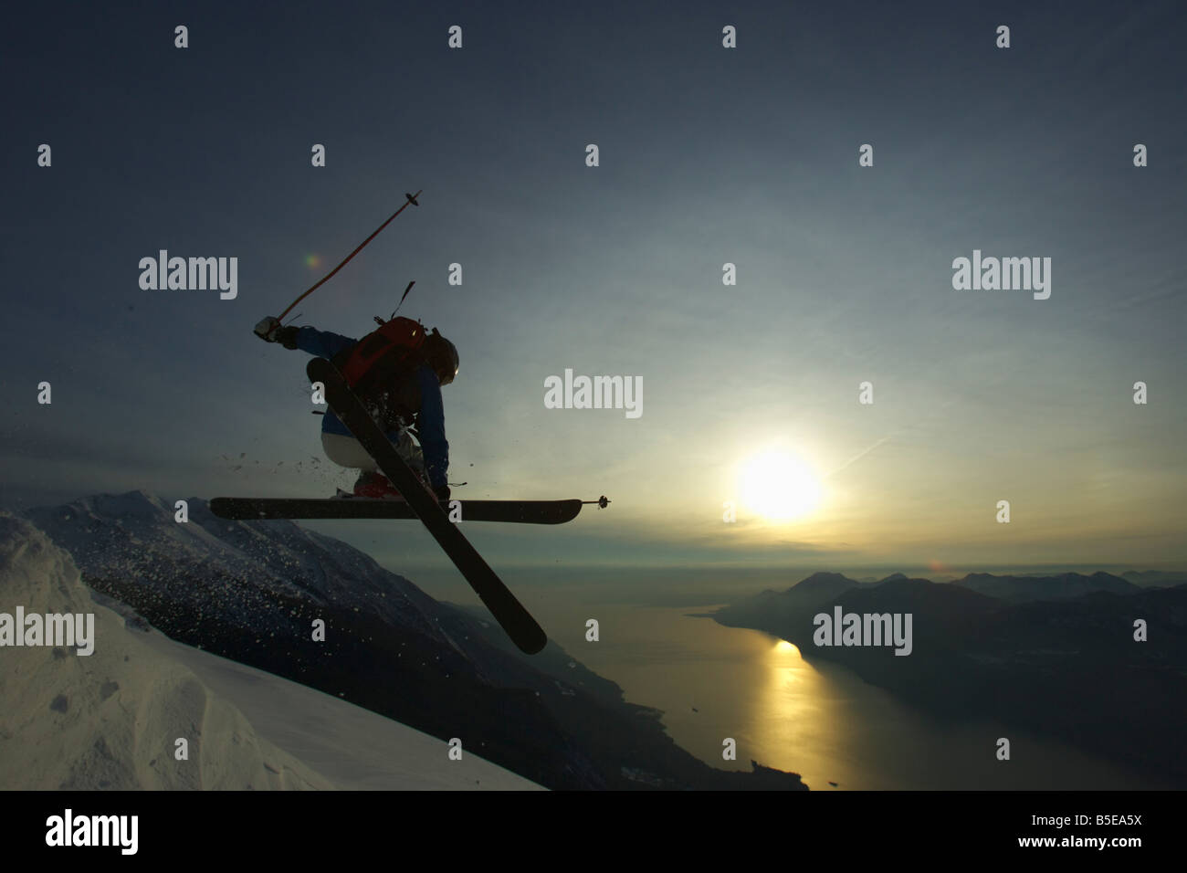 Jumping skier in front of sunset - Stock Image