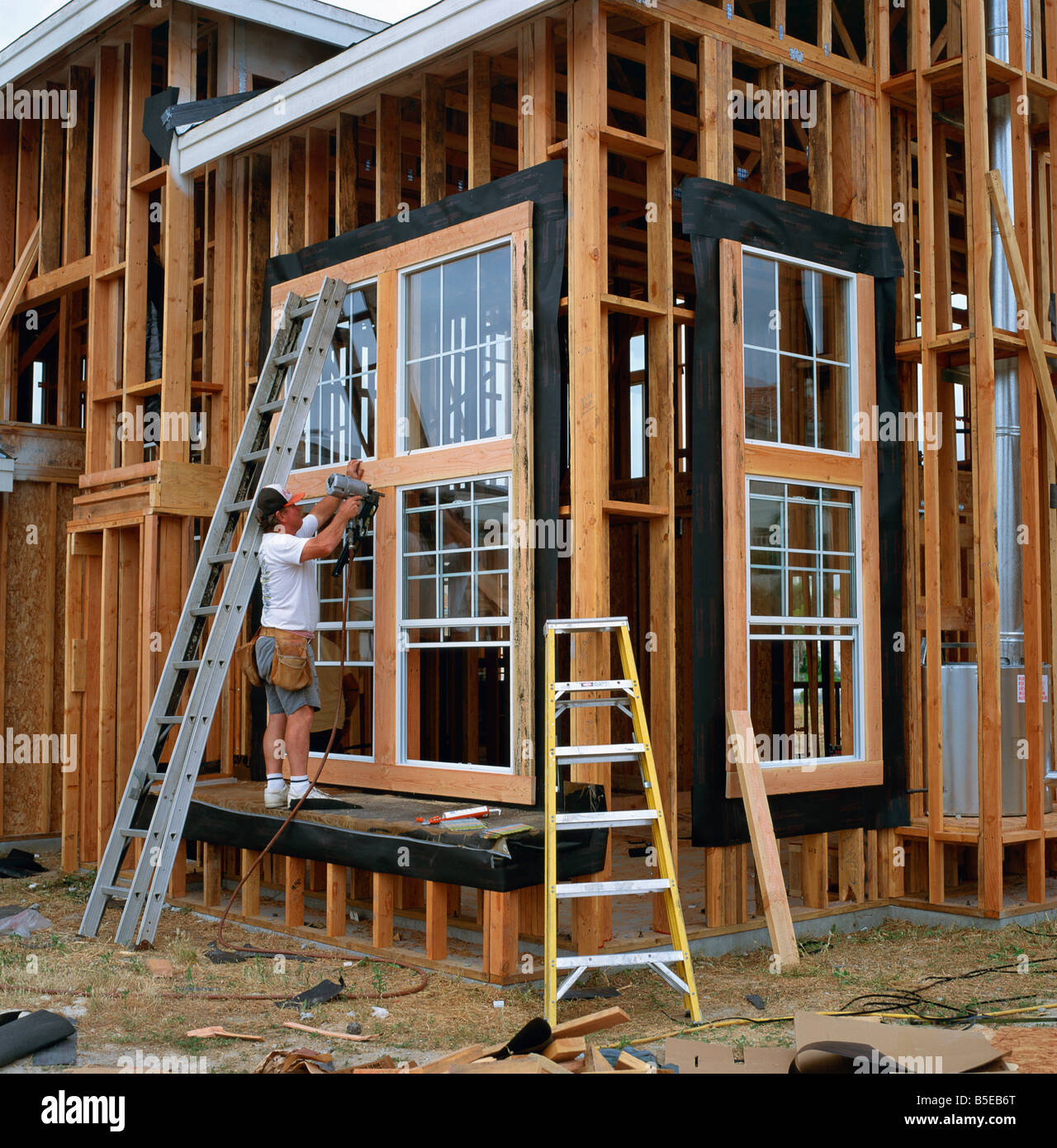 Man using a drill in the construction of a wood framed house in California USA T Gervis - Stock Image