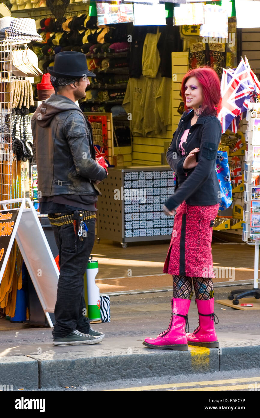 London , Camden Lock Market pretty female punk girl with pink hair skirt , tattoo & laced boots & pierced - Stock Image