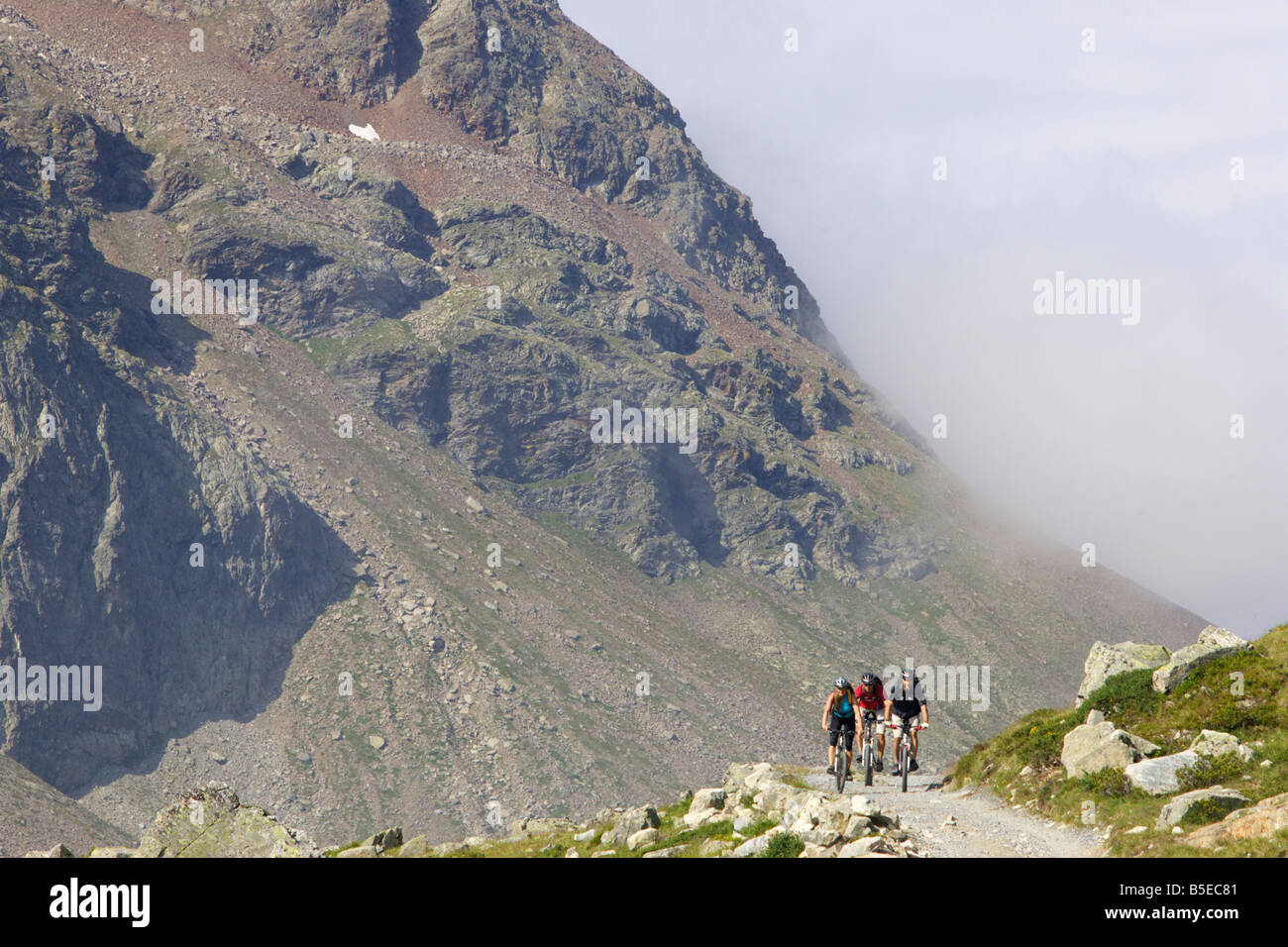 Three cyclists in a mountain coulisse - Stock Image