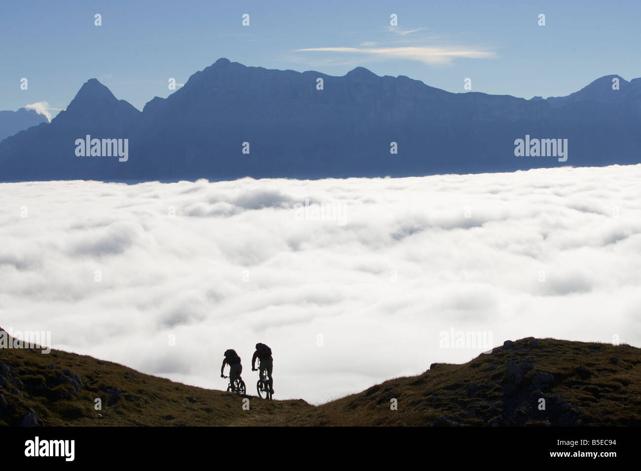 Two mountainbikers in front of a cloud cover - Stock Image