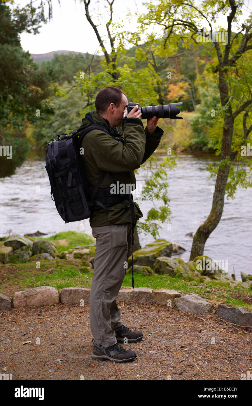 Photographer using a D300 with Nikon 70-200mm VR lens outside by river Scotland UK - Stock Image
