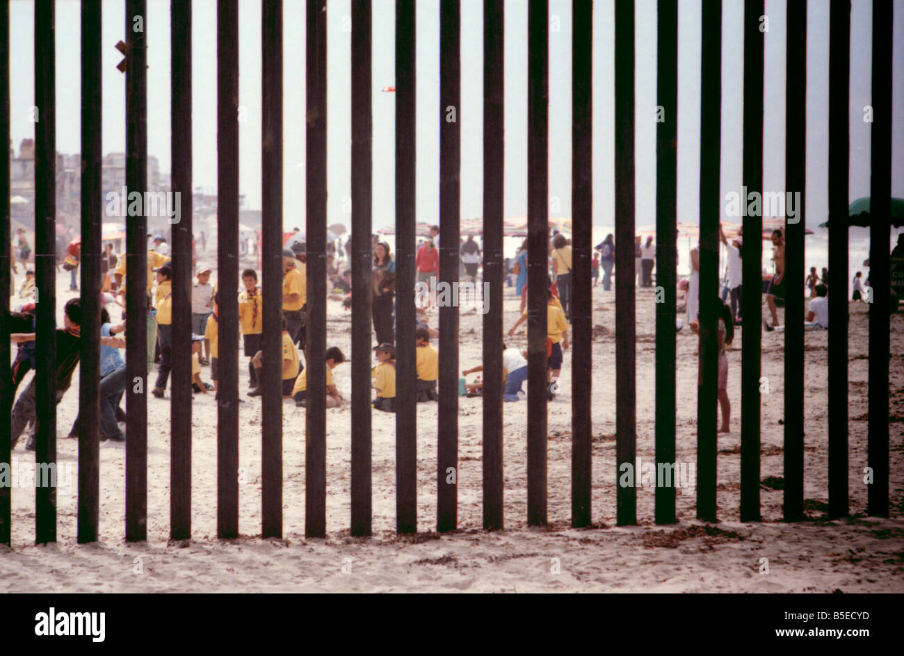 The fence and people in Mexico at the International Border at Border Field State Park. - Stock Image