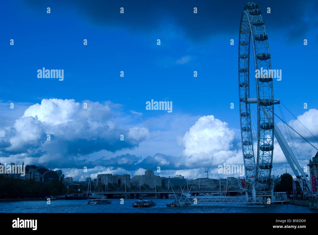The London Eye shot from Westminster Bridge with blue sky and dark clouds with an overall view of the southbank - Stock Image