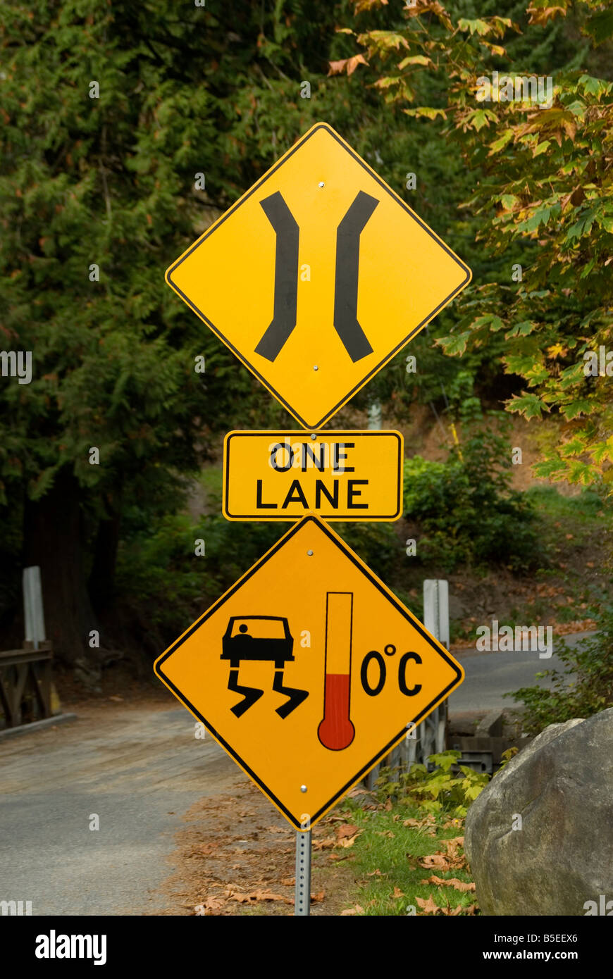 Road Signs Warning of a One Lane Bridge Ahead and Slippery When Cold. - Stock Image