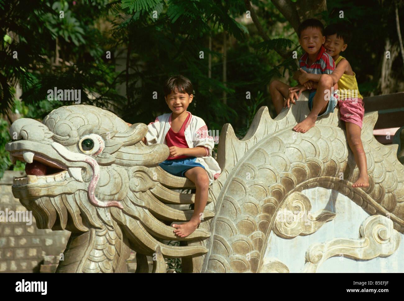 Children sitting on dragon Long Son Pagoda Nha Trang Vietnam Indochina Southeast Asia Asia Stock Photo