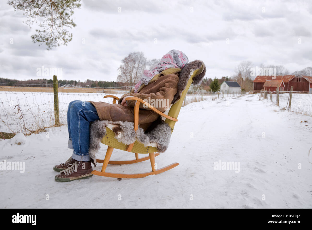 A man sitting in a sheepskin covered rocking chair in a country lane with a hippie type scarf covering his face - Stock Image