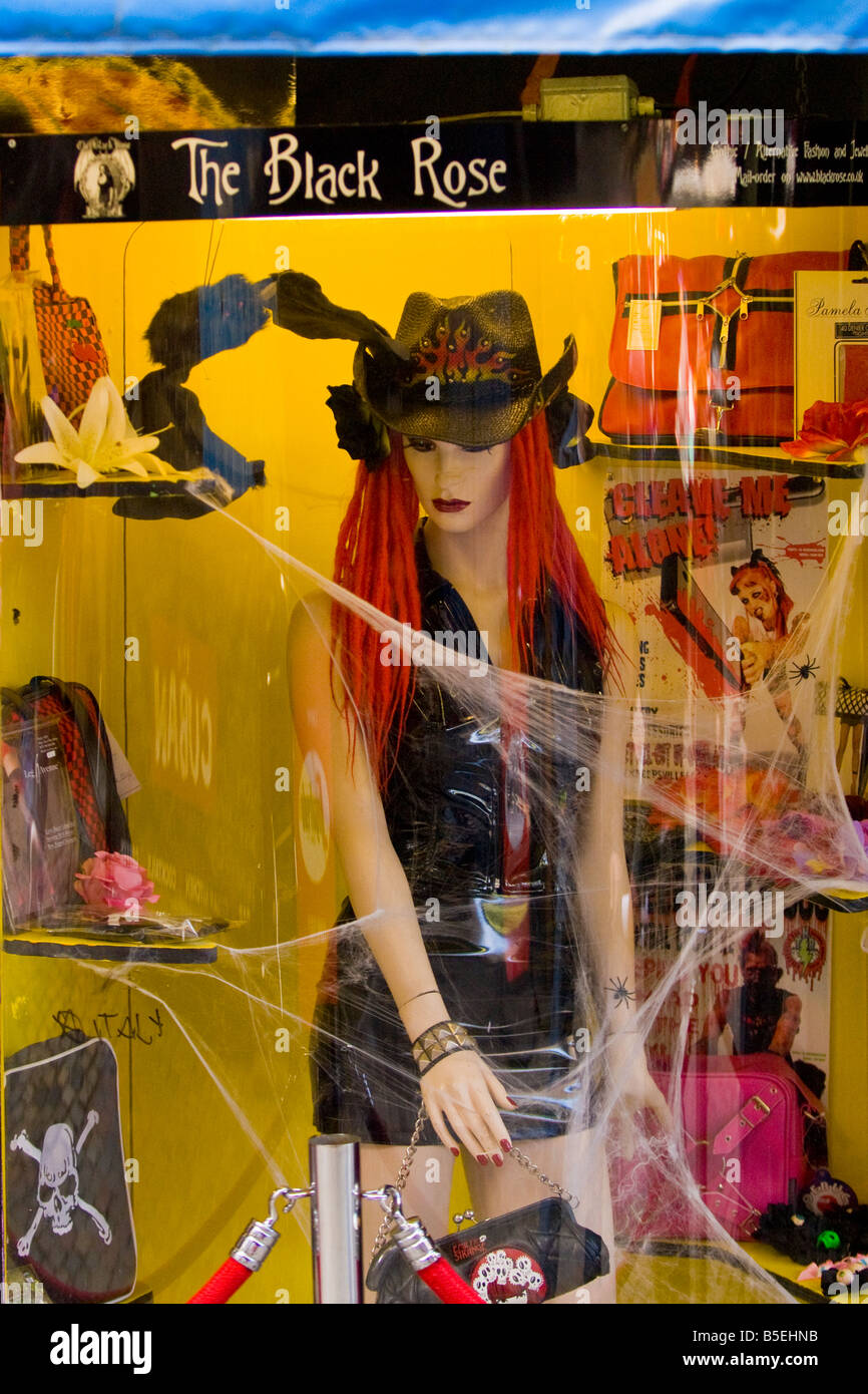 Camden Stables Market shop window of The Black Rose with female model in black PVC plastic minidress & cowboy - Stock Image