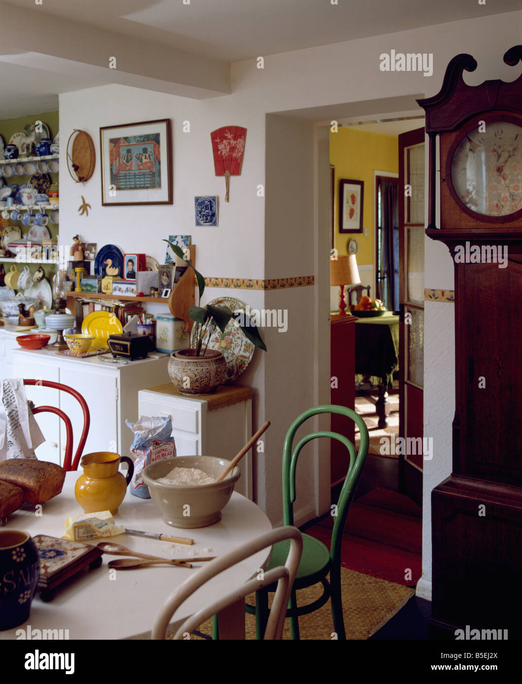 Longcase Clock In Cottage Kitchen With Painted Red And Green Bentwood Chairs  At Table With Cake Making Ingredients