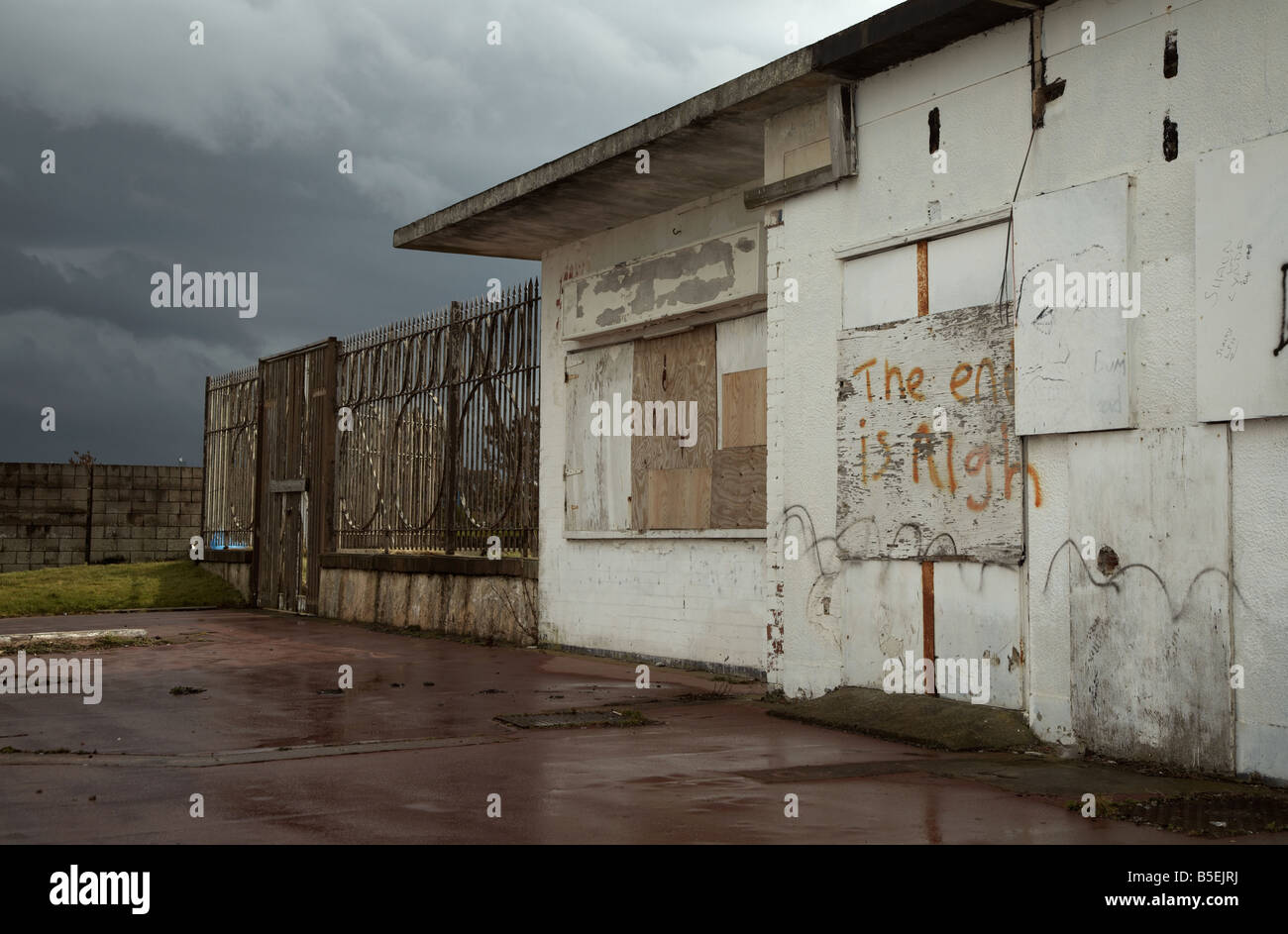 boarded up refreshment stall at an english seaside town morecambe on a stormy day with prophetic graffiti saying - Stock Image
