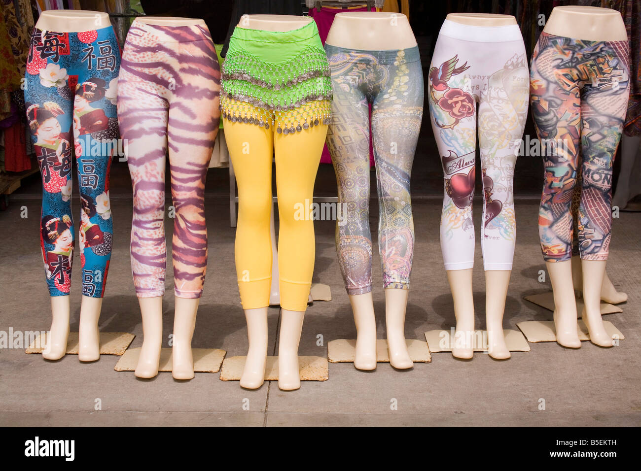 A group of mannequin legs displayed outside a casual clothing shop, each wearing a different pair of colorful leggings - Stock Image