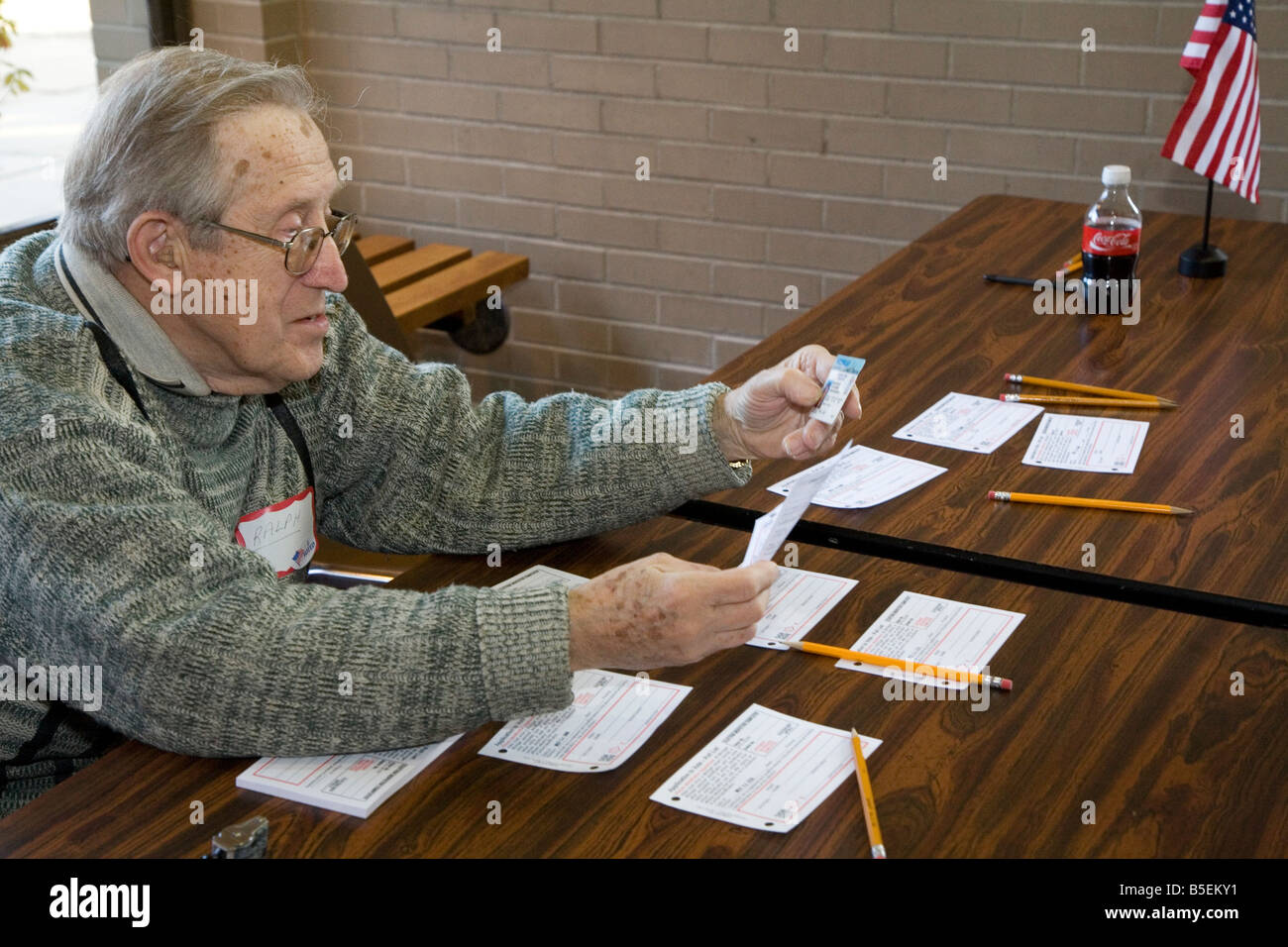 Election official checks voter's identification - Stock Image