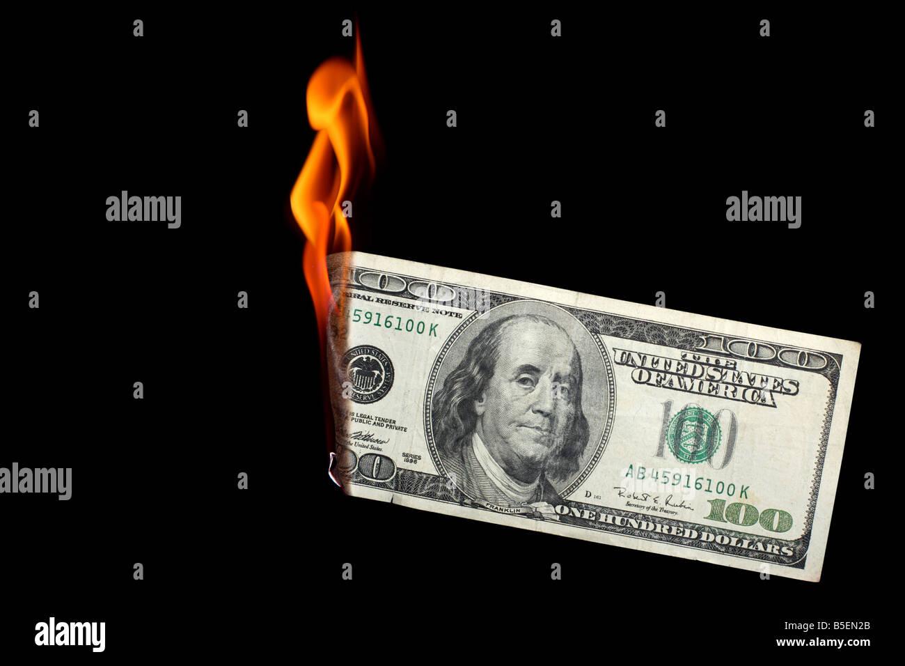 One hundred dollar bill burning on black background Stock Photo