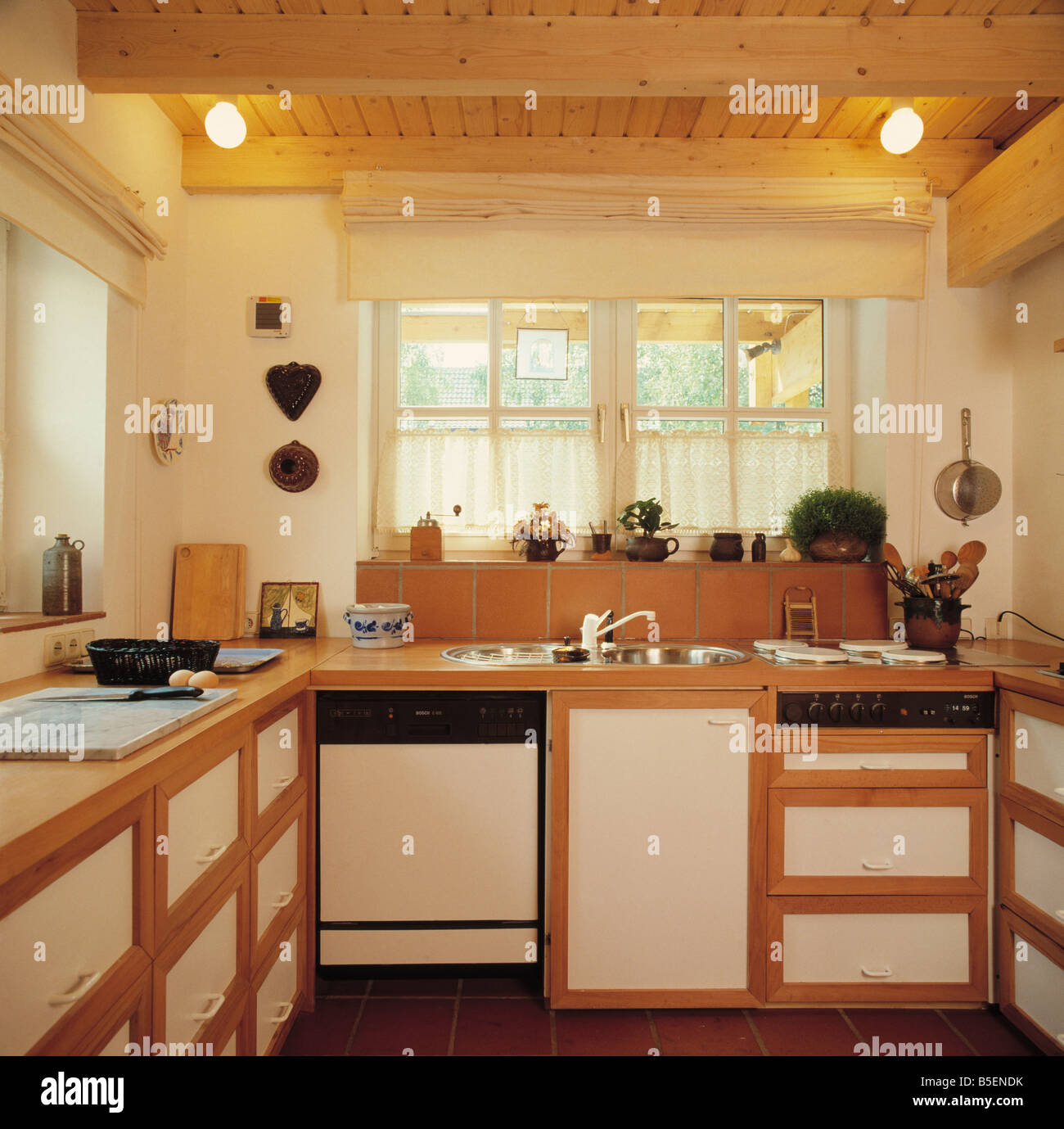 Lighting On Wooden Ceiling In Small Kitchen With Sink And Dishwasher In  Simple Fitted Unit Below Window With Lace Curtains