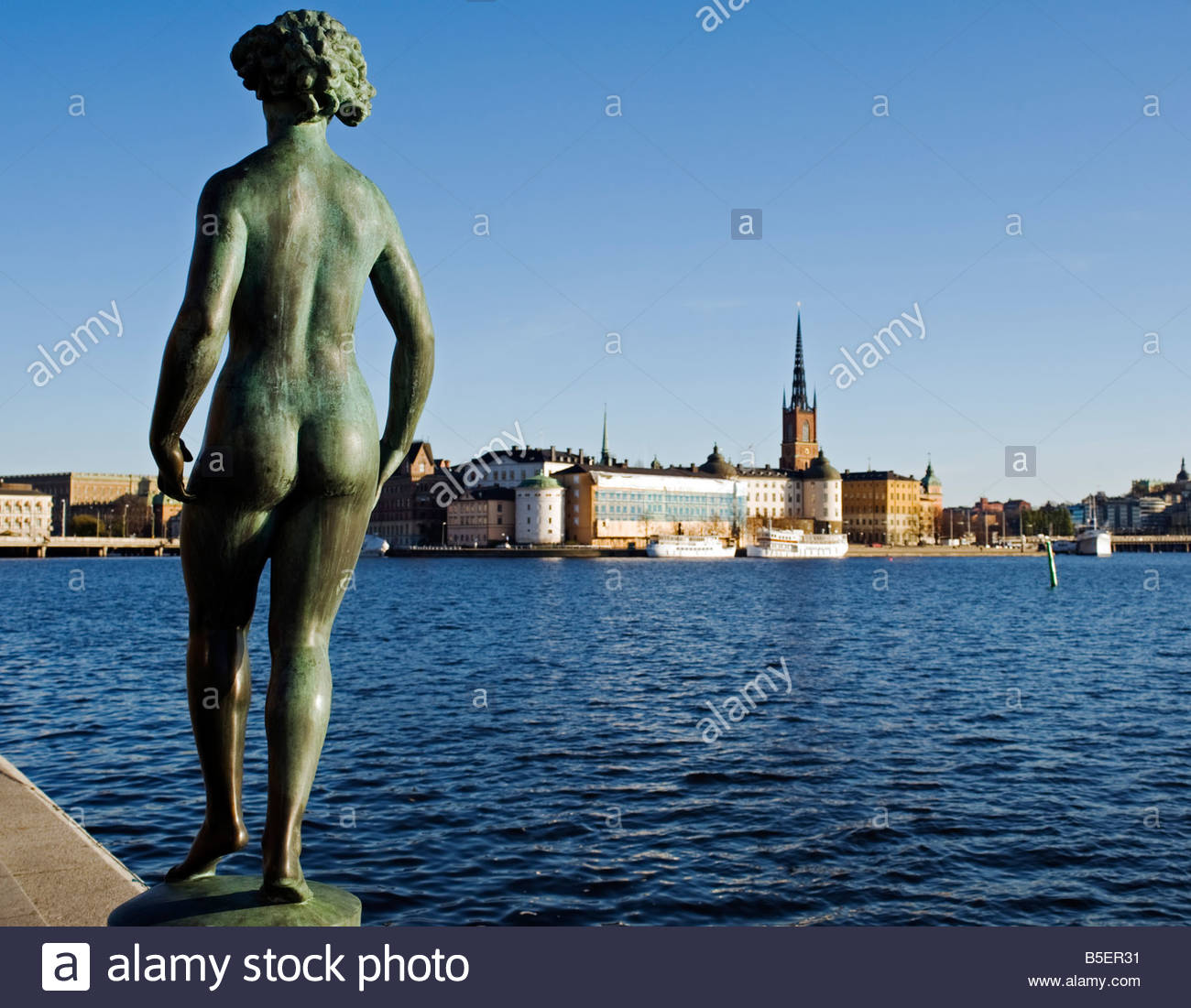 Statue in front of Stadshuset in front of the Stockholm Town Hall by Carl Eldh Stockholm with Riddarholmen to rear - Stock Image