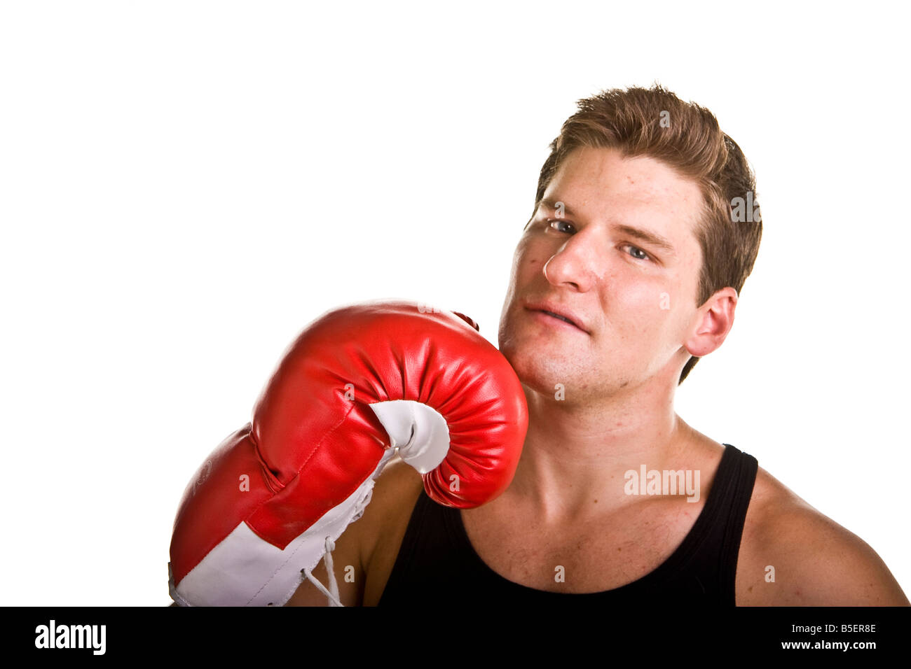 32e9fc3d77e4f An athletic looking young man in black tank top wearing red boxing gloves  with one glove on chin