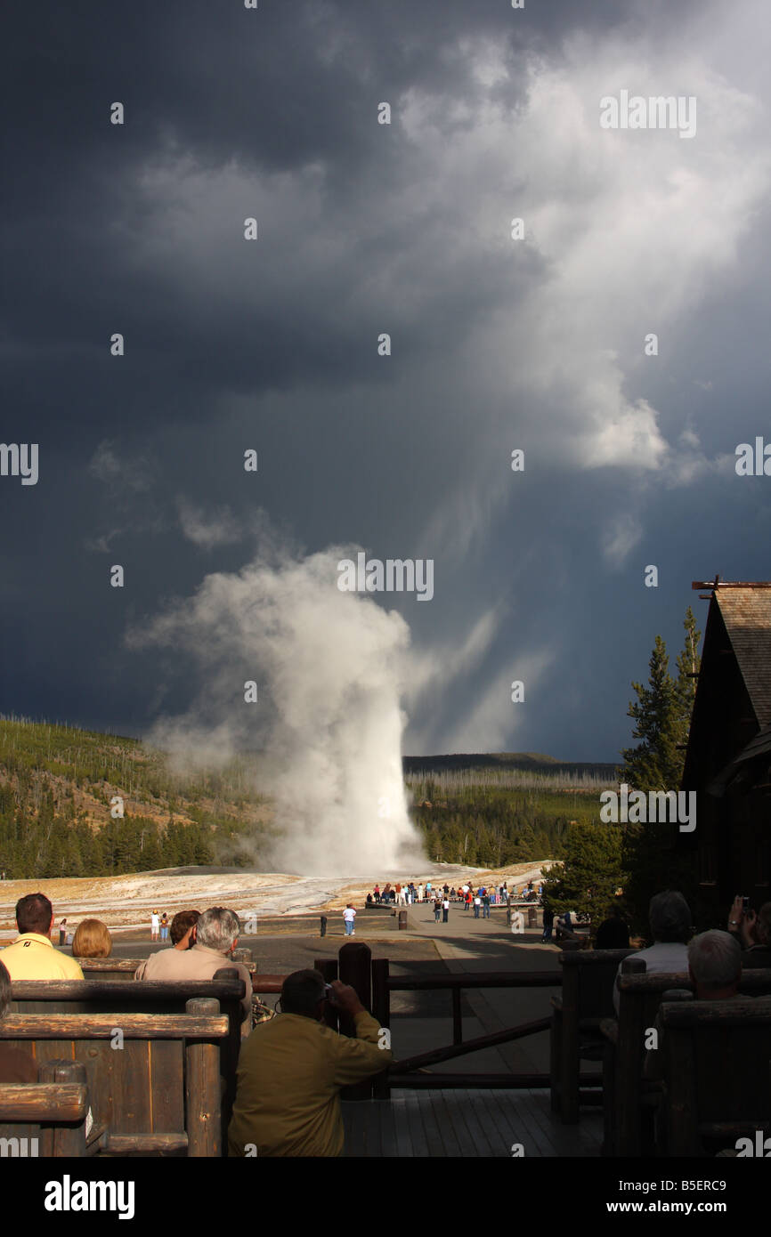 Watching Old Faithful erupt from the viewing deck of the Old Faithful Inn, Yellowstone National Park, Wyoming - Stock Image