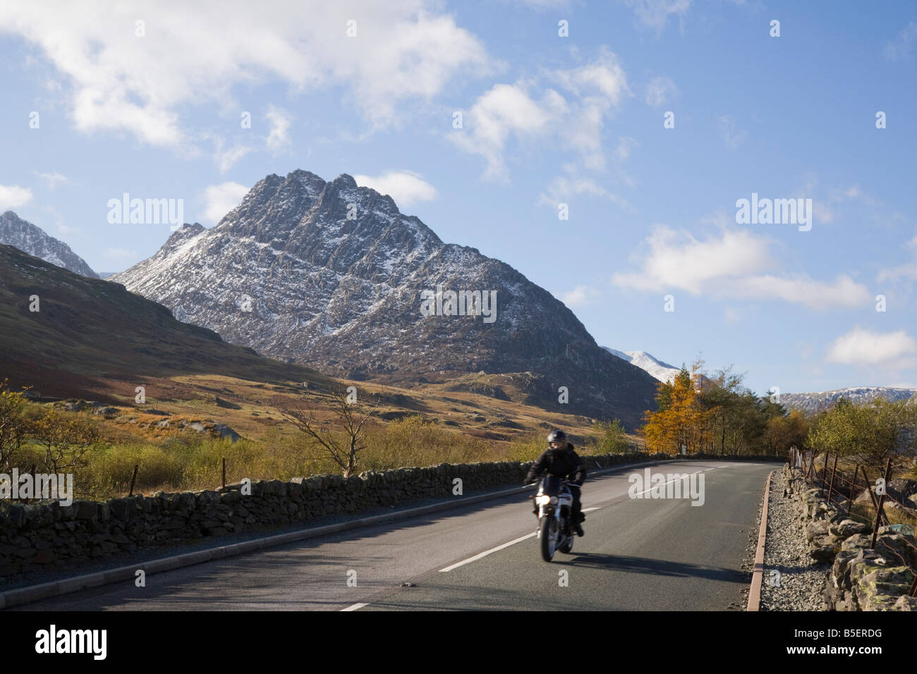 View along historic A5 road with motorbike riding through Ogwen Valley to Tryfan mountain in Snowdonia National - Stock Image