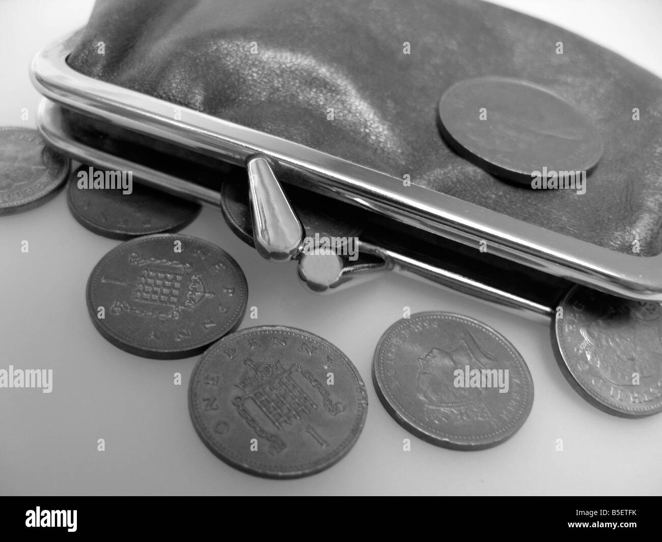 battered old purse with coins in the credit crunch hardship times - Stock Image