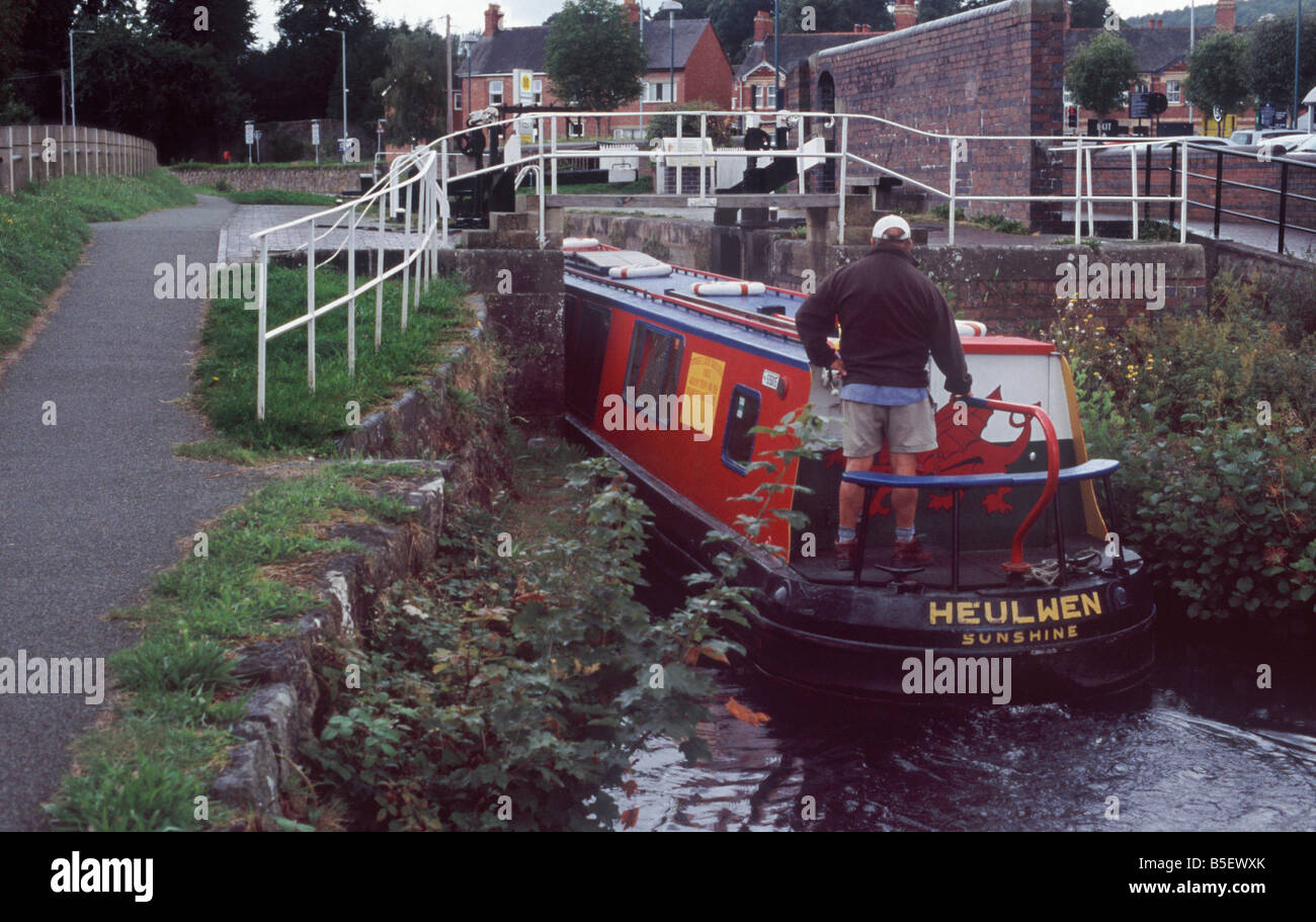 Man steering narrowboat into lock in the centre of Welshpool on the Montgomery Canal, Powys, Wales Stock Photo