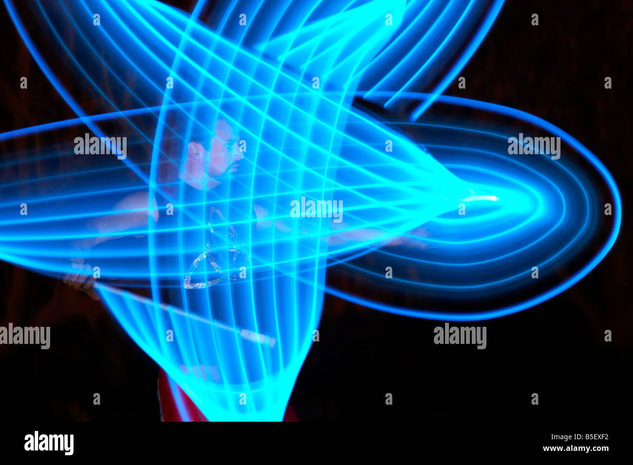 man juggling LED lightstick playing with lights - Stock Image