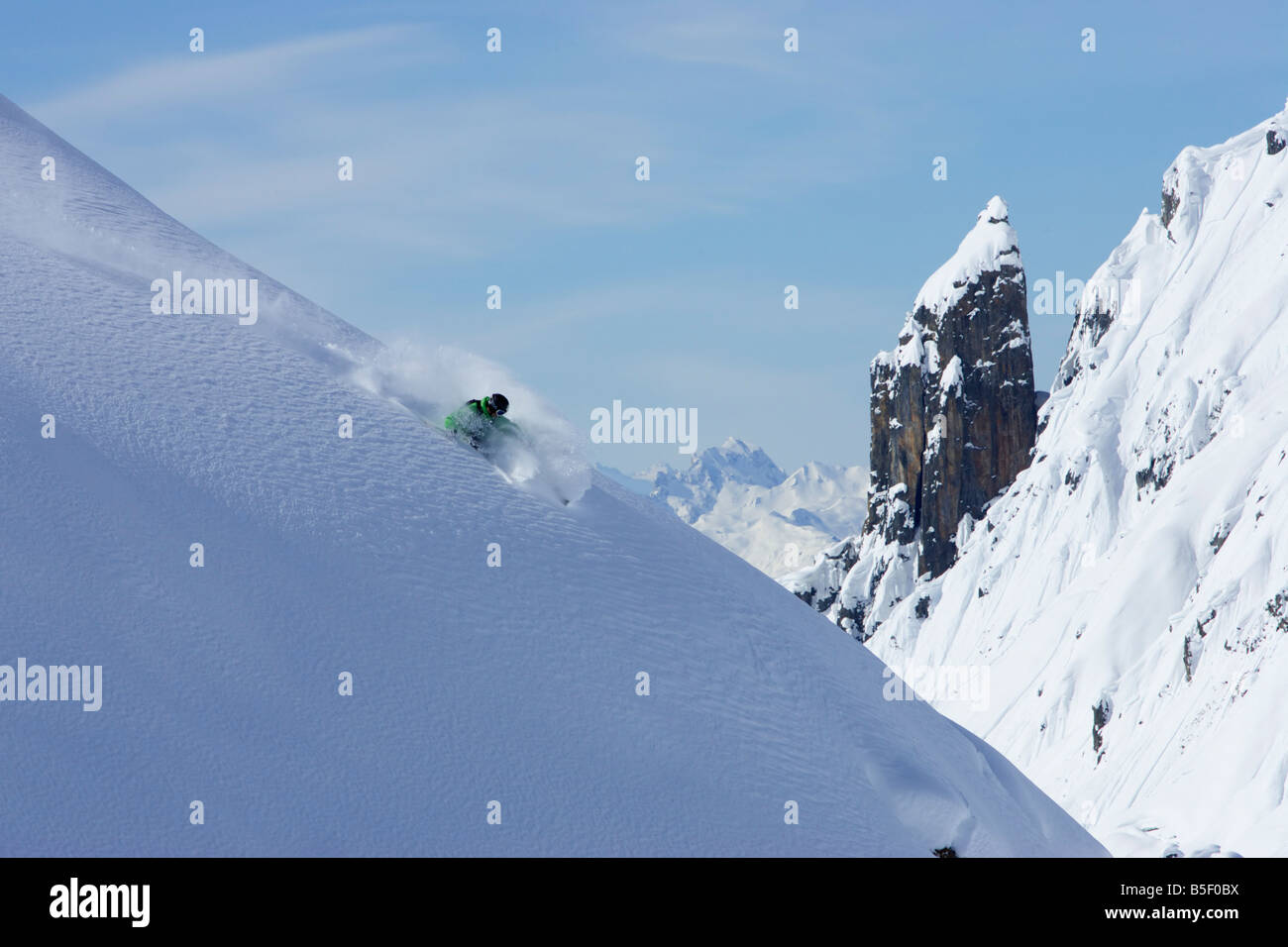 Skier doing a tight turn on intact snow - Stock Image