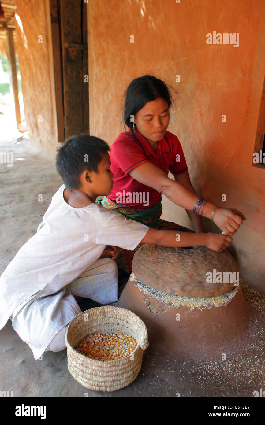 Nepal: mother and son grinding rice with a stone grinder in a village in the Himalaya mountains - Stock Image