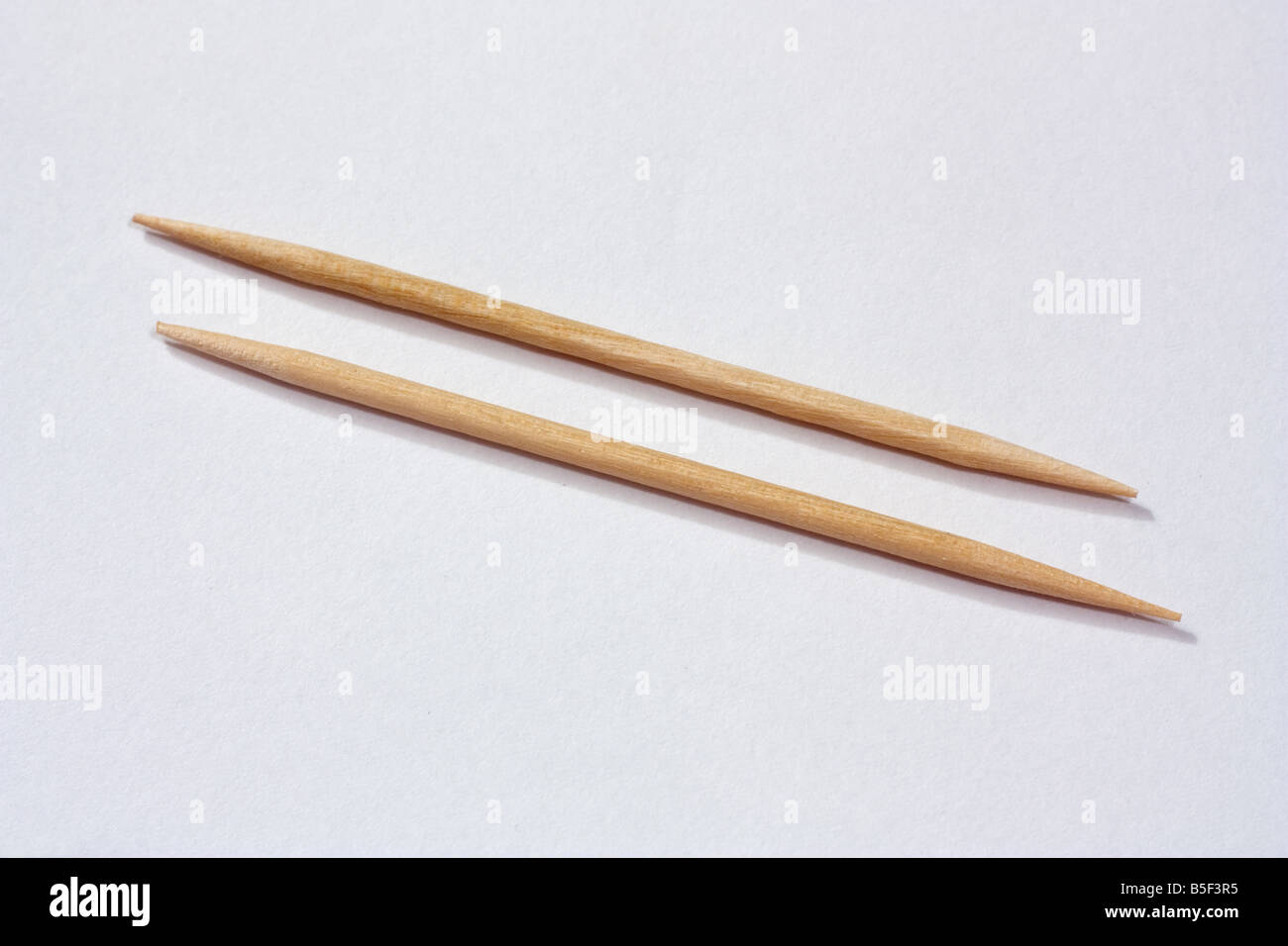 A close up shot of two toothpicks laid in parallel - Stock Image