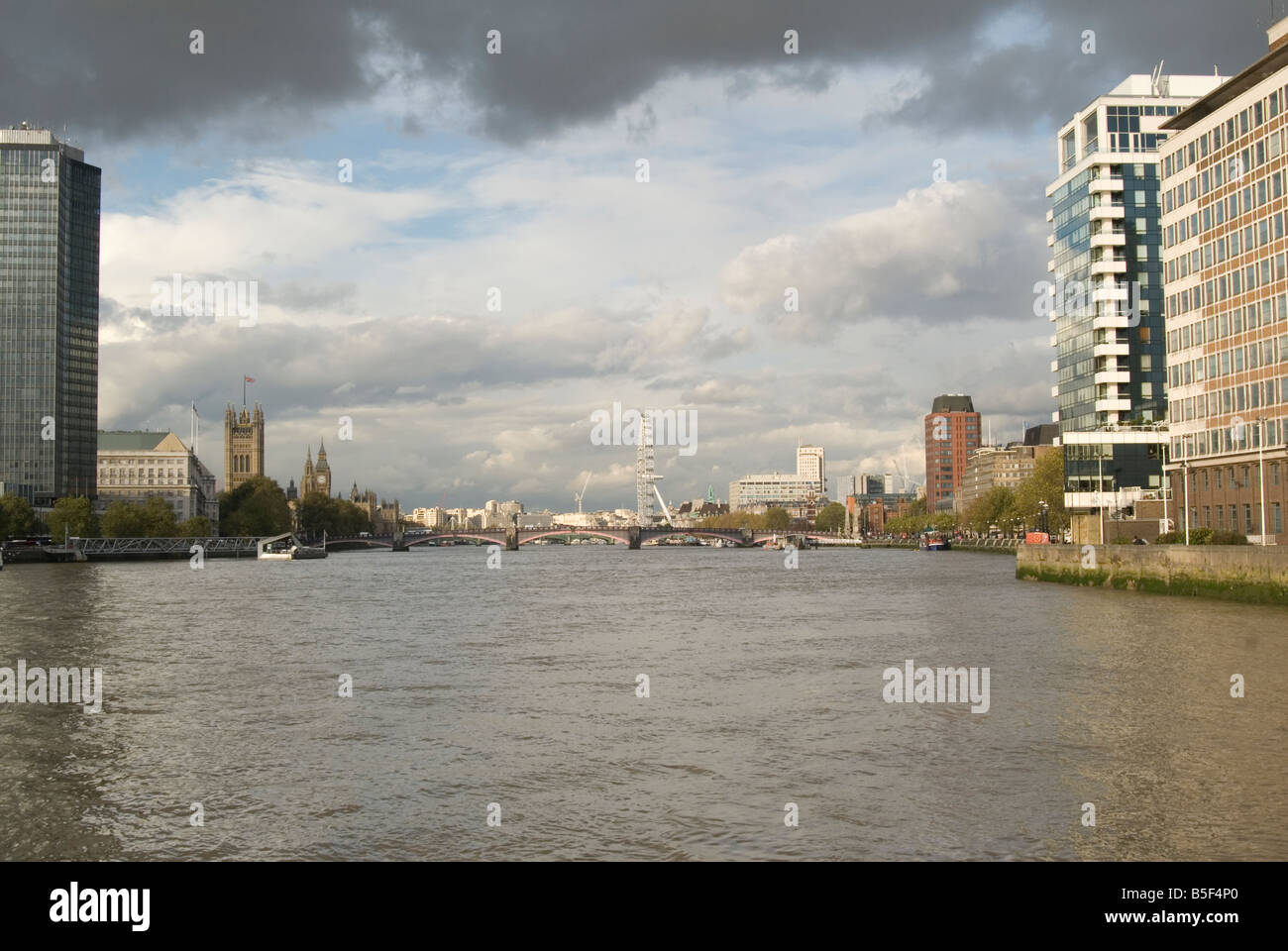 A shot looking down the Thames River towards the South Bank with buildings on both sides, and a rain cloud is forming - Stock Image