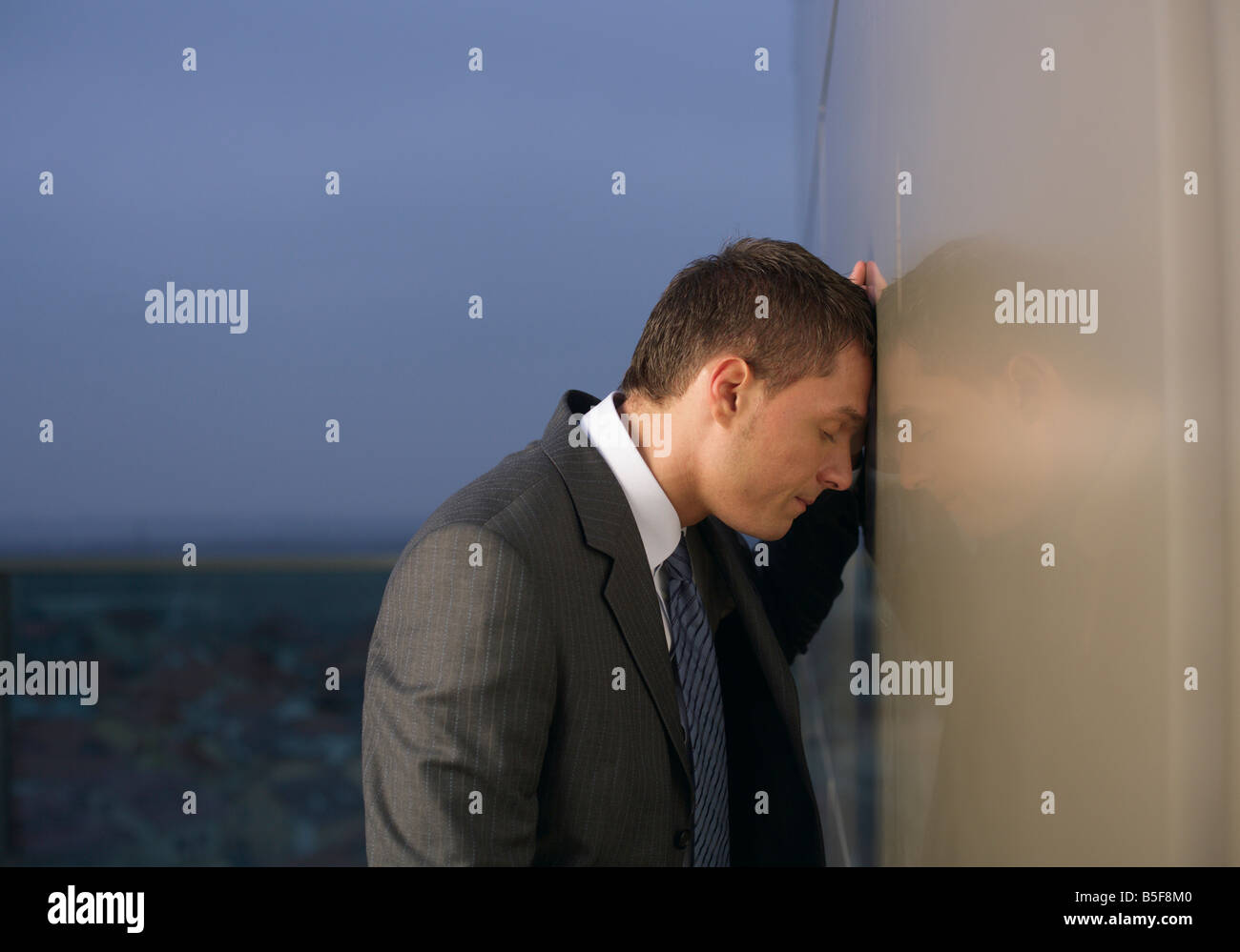 Despaired businessman leaning against wall - Stock Image