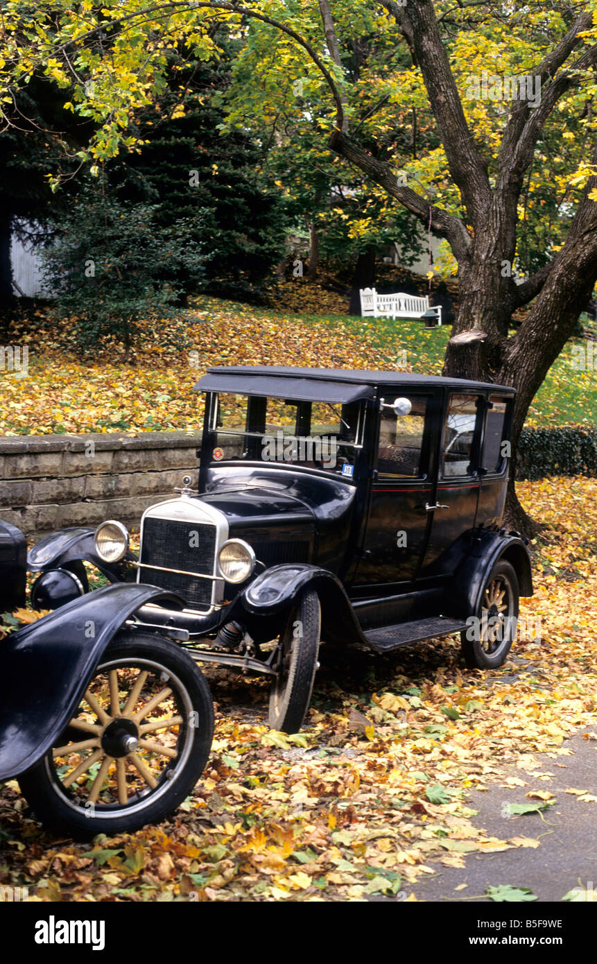 Antique Ford Model T closed top cars parked along side street in Harpers Ferry, WV, with autumn leaves on the road. - Stock Image
