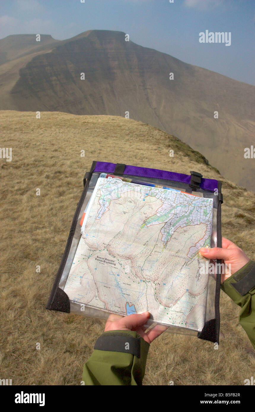 A walker holding out a map in the Brecon Beacons - Stock Image