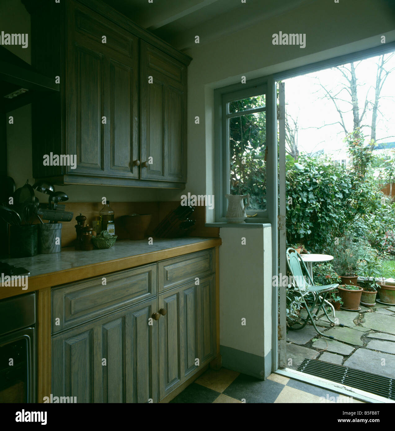 Pale Grey Woodstain Units In Kitchen With Patio Door Open To The - Grey wood kitchen doors