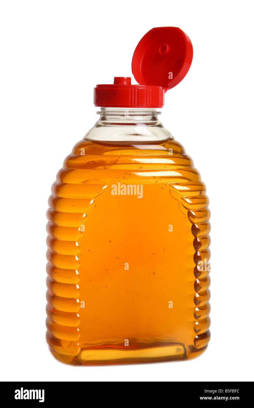 Bottle of honey cutout on white background - Stock Image