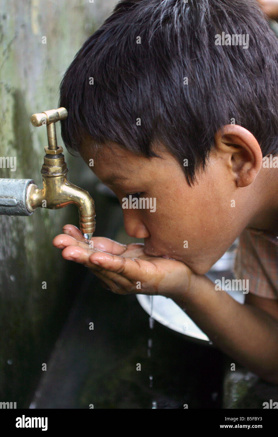 Nepal: Boy drinks from a waterpipe - Stock Image